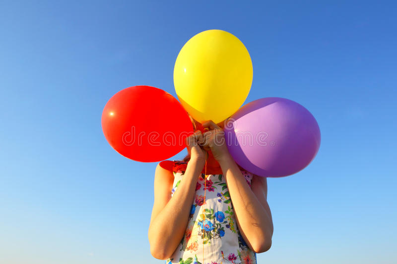 The girl covers her face with balloons. Shyness,shame,resentment stock image