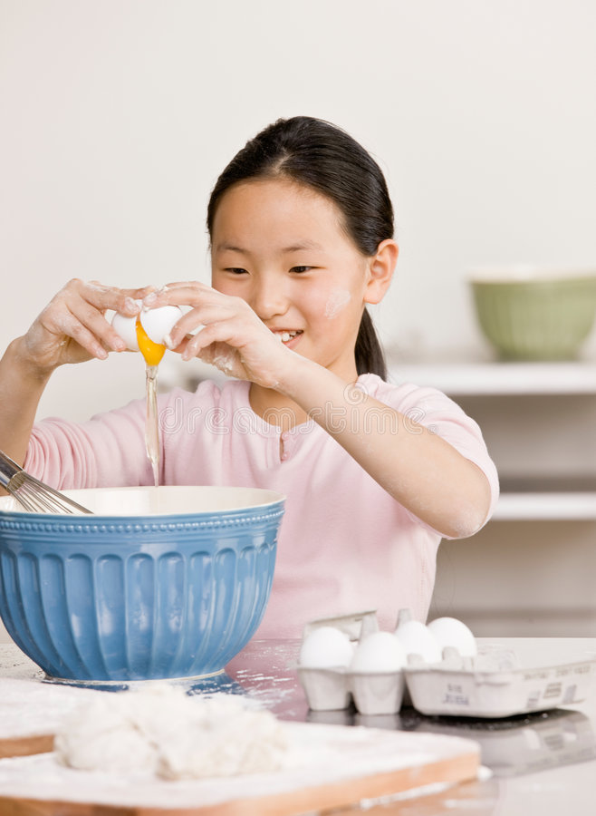 Girl cracks eggs into bowl for baking project. Girl cracks eggs into bowl in kitchen for baking project royalty free stock image