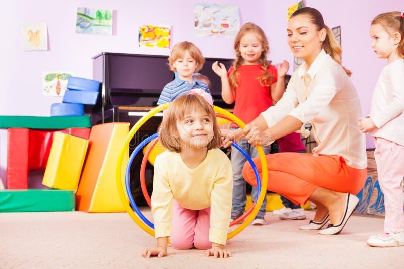 Girl crawl in plastic hoop, kindergarten group royalty free stock photos