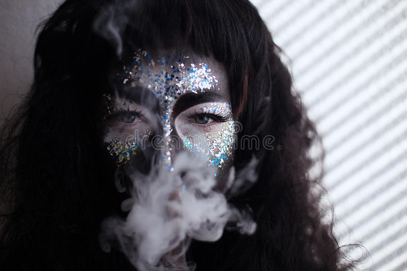 Girl with creative face art makeup smoking. Portrait of a girl with creative black face art makeup smoking royalty free stock photo