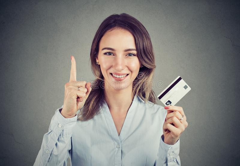 Girl with credit card holding finger up. Young formal woman having best banking offer holding finger up and showing new credit card smiling at camera stock photos