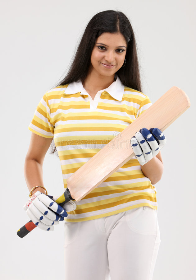 Girl with cricket bat and gloves. Beautiful girl with cricket bat and gloves stock photo