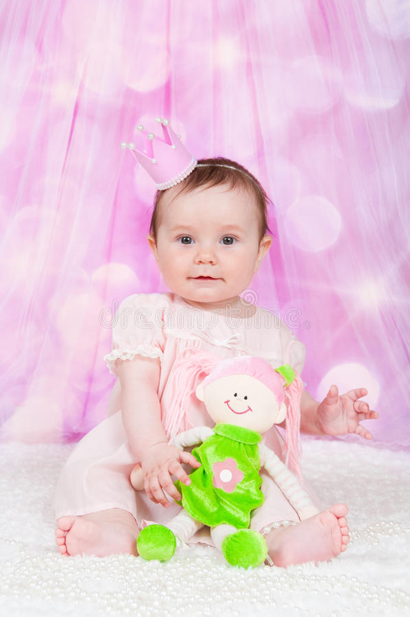 Girl with a crown, sitting on a pink background with bokeh. stock image