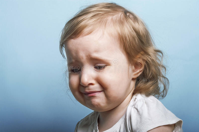 Girl crying. Emotional portrait of a two years old girl ready to burst to cry, blue background studio shot stock photo