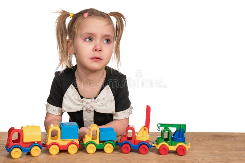 Girl is crying while playing. Little girl crying playing toy cars on a trailer, sitting at a wooden table, isolated on a white background royalty free stock images