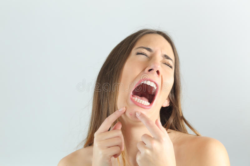Girl crying while pressing a pimple on her chin. With a grey background royalty free stock photography