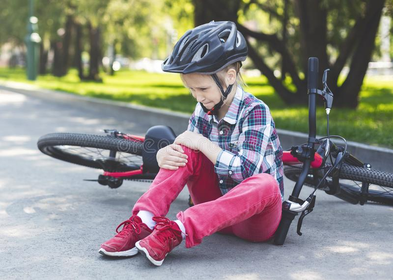 Crying girl is sitting next to her bike stock photography