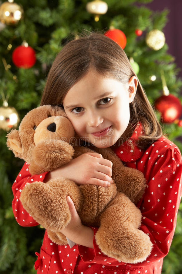 Girl Cuddling Bear In Front Of Christmas Tree royalty free stock photography