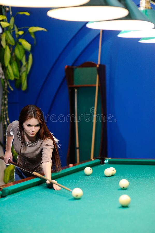 Girl with a cue in her hands playing billiards stock photo