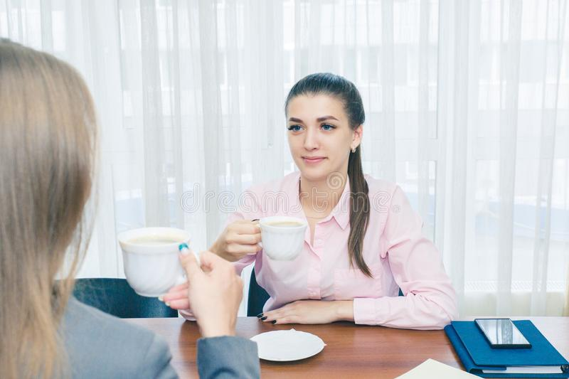 Girl with a Cup of coffee. A girl in a pink blouse drinking coffee in the office. Smiling girl with coffee. Two royalty free stock images