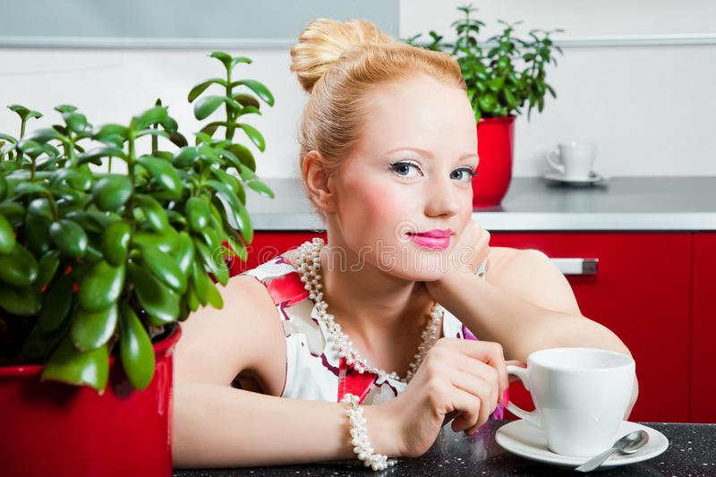 Girl with cup of morning coffee in interior of kit