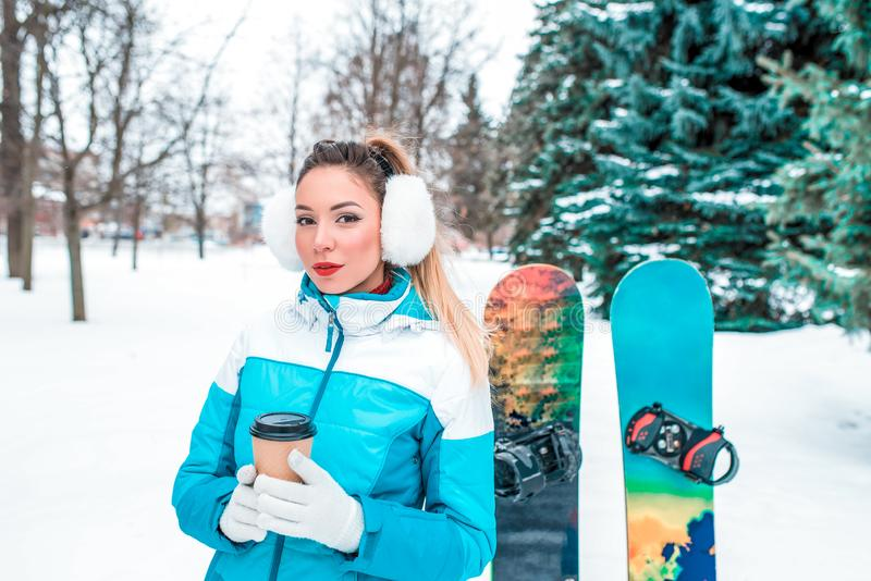 A girl with cup tea coffee, in white warm ears, is standing in a winter park against background of Christmas trees and royalty free stock images
