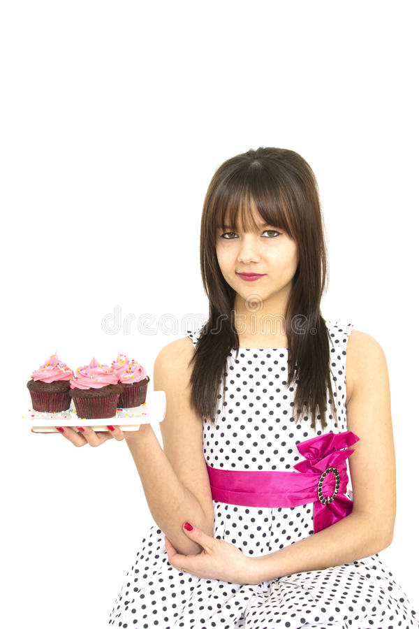 Girl with cupcakes. Teenager with a vintage polka dots dress holding a plate with pink cupcakes royalty free stock photo