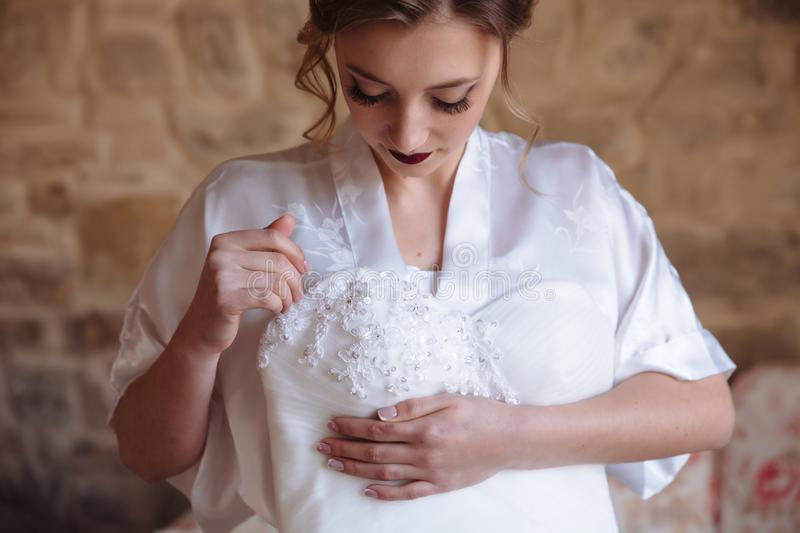 A girl with curls and long eyelashes looks down at her wedding dress, which she holds with her hand. The bride admires. The embroidery, patterns and fabric of royalty free stock images