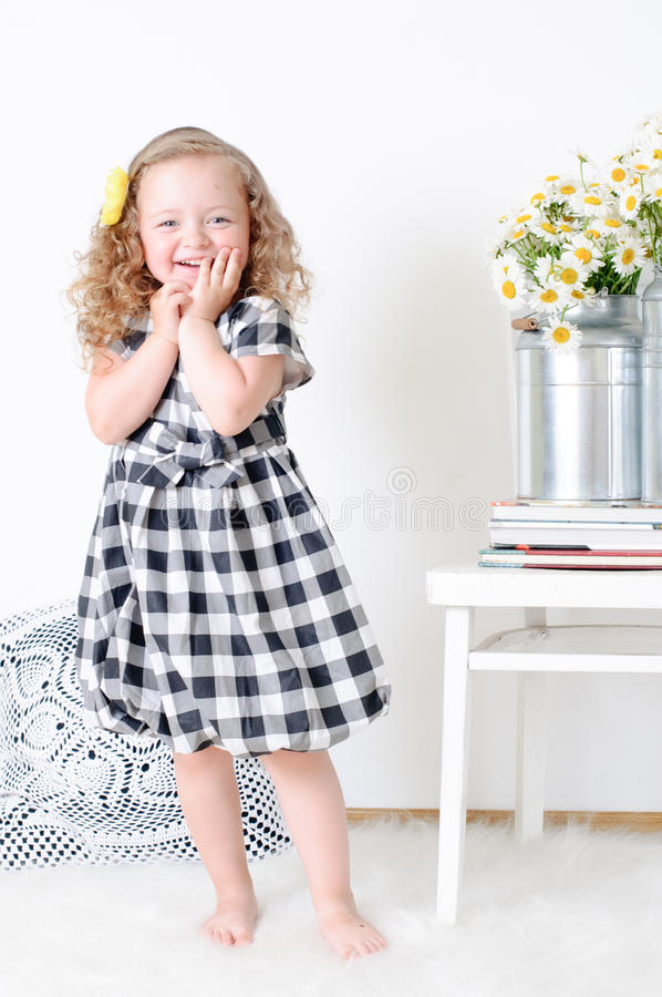 Girl with curly hair. A girl with curly hair in a checkered dress in a white room royalty free stock images