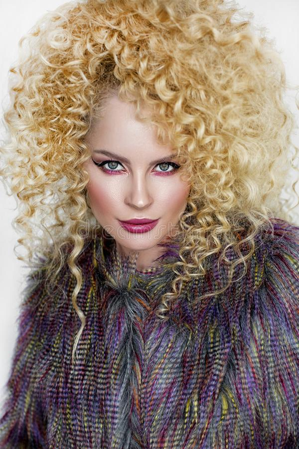 Girl with curly hair. Beautiful blonde girl with curly hair in purple fur coat on white smiling background stock photos