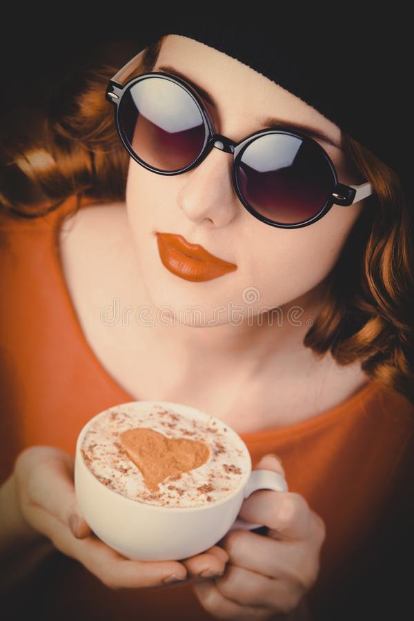 Girl with curly hair holding a cup of coffee stock photos