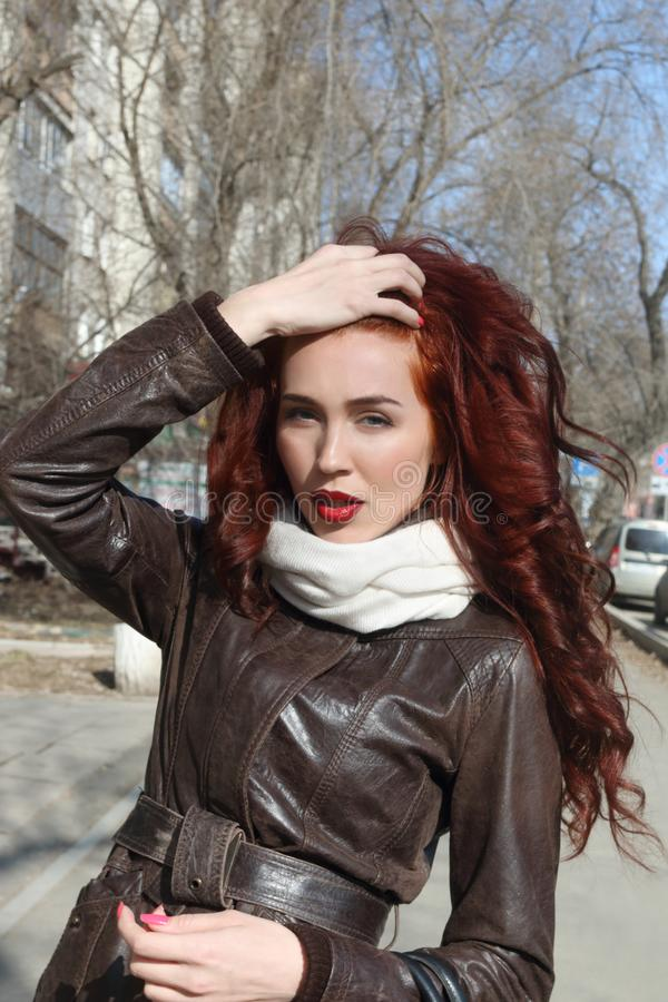 Girl with curly hair in jacket poses outdoor royalty free stock images