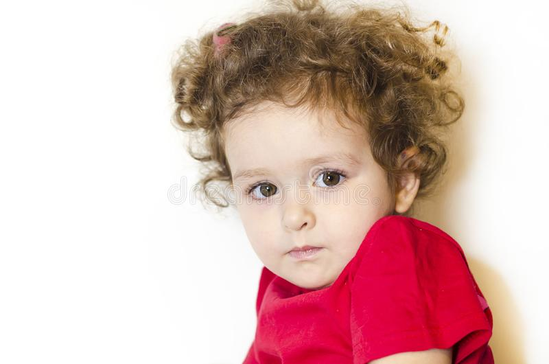 Girl with curly hair and long eyelashes. kid looks thoughtfully at the camera. baby in festive red clothes. human emotions stock image
