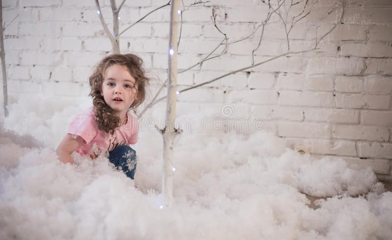 The girl with curly hair plays with artificial snow. Winter, festive atmosphere stock images