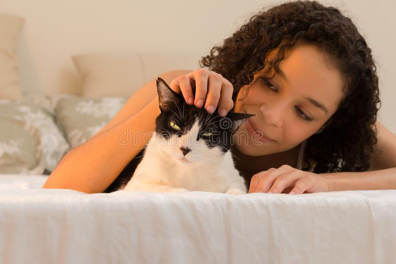 Girl with curly hair smiling at domestic cat pet in bed. Concept of love to animals, pets, lifestyle, care, tranquility, peace,. Portrait of girl with curly hair stock image