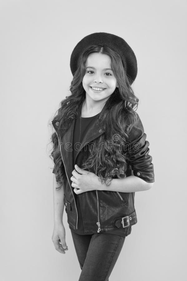 Girl curly hair wear leather jacket. Little rock star concept. Brutal style tender but confident girl. Rock style suits stock photography