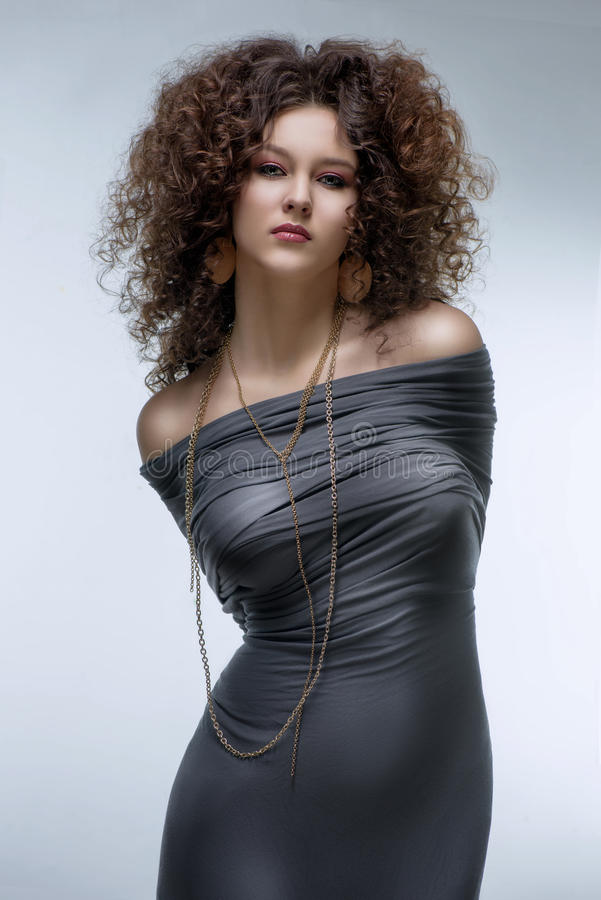 Girl with a curly hairstyle, modern make-up and carnivore look. Brunette girl with a curly hairstyle and carnivore look with her hands tied stock photography