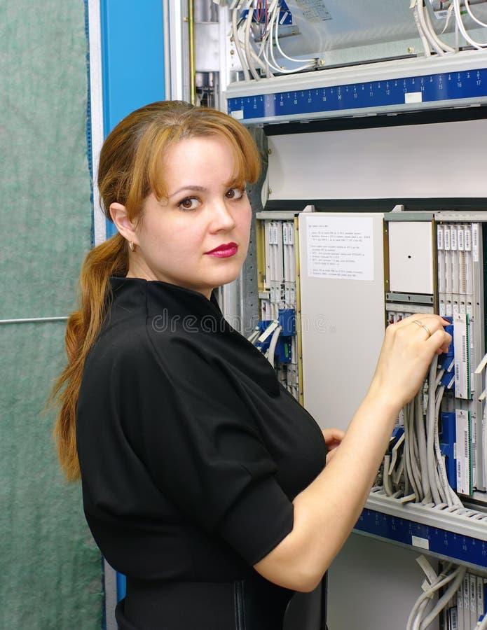 Girl customer engineer of exchange. Woman engineer serves equipment on digital telephony station royalty free stock photos