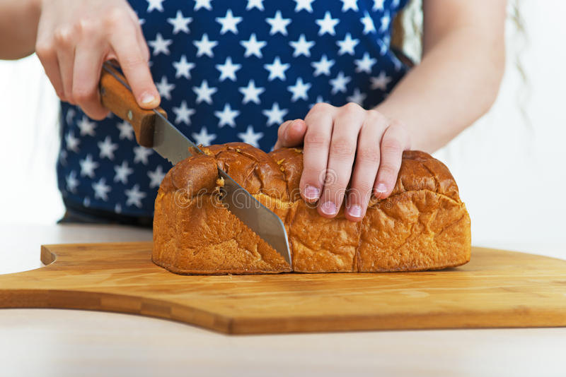Girl cut bread with knife royalty free stock photography