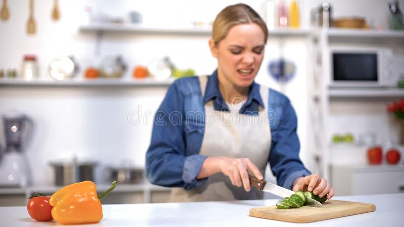Girl cut finger by accident while slicing cucumber in kitchen, household injury royalty free stock photography