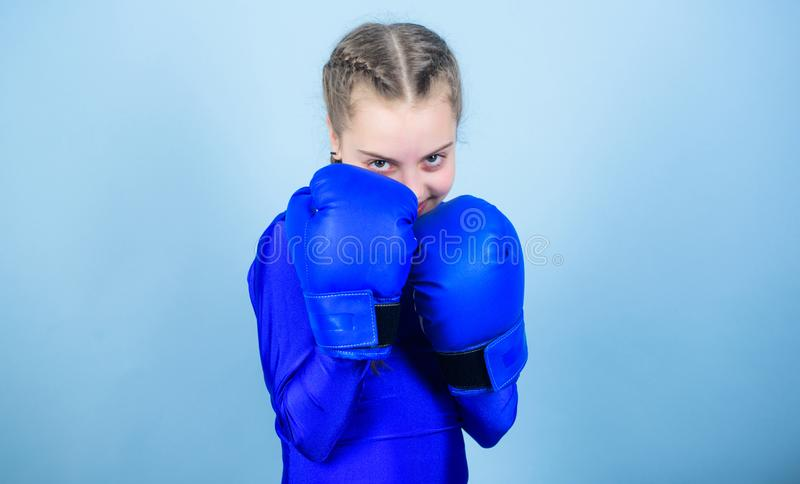 Girl cute boxer on blue background. With great power comes great responsibility. Boxer child in boxing gloves. Rise of. Woman boxers. Female boxer change royalty free stock image