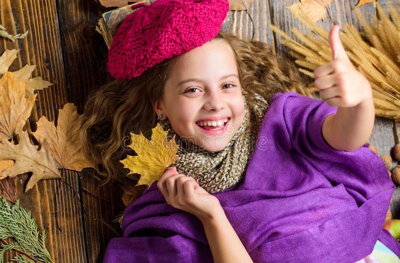 Girl cute child in knitted hat lay wooden background fallen maple leaves top view. Autumn fashion hat accessory. Kid. Girl bright soft knitted hat enjoy autumn stock photography