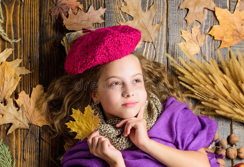 Girl cute child in knitted hat lay wooden background fallen maple leaves top view. Fashion hat trend fall season. Kid royalty free stock image