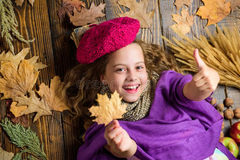 Girl cute child in knitted hat lay wooden background fallen maple leaves top view. Kid girl bright soft knitted hat. Enjoy autumn. Fashion hat trend fall season stock photography