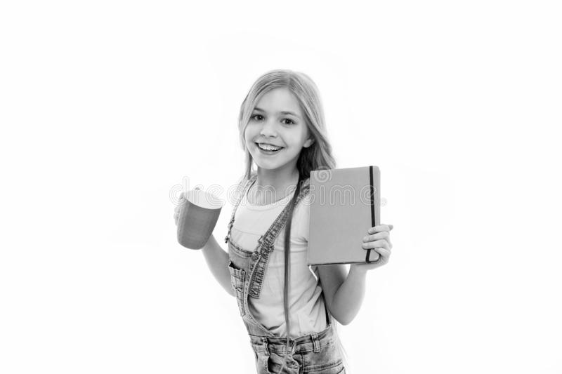 Girl cute child long hair drink cocoa or tea. Schoolgirl with book or notepad and mug having tea break. Water balance royalty free stock image