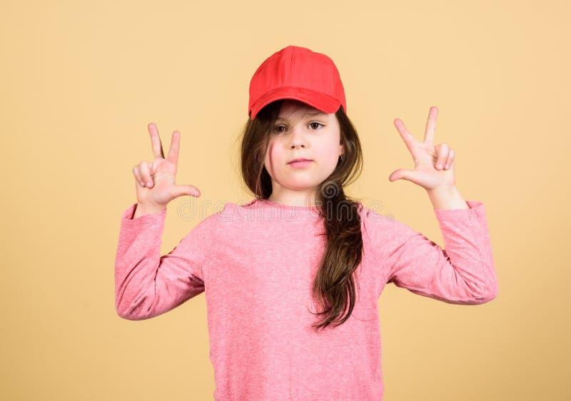 Girl cute child wear cap or snapback hat beige background. Little girl wearing bright baseball cap. Modern fashion. Kids stock images