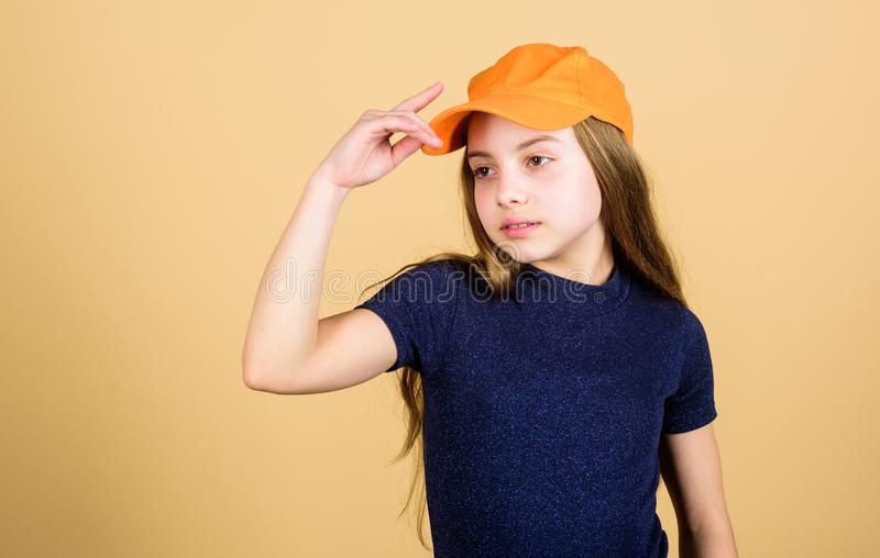 Girl cute child wear cap or snapback hat beige background. Little girl wearing bright baseball cap. Modern fashion. Hat. Or cap. Stylish accessory. Kids fashion royalty free stock photography