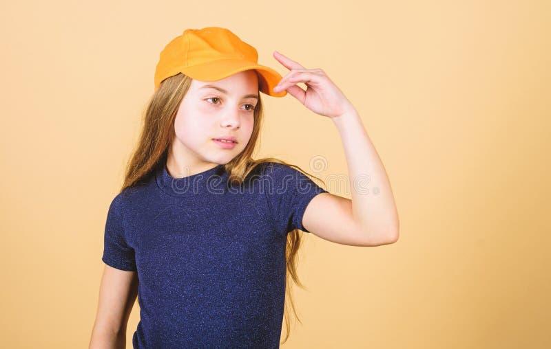 Girl cute child wear cap or snapback hat beige background. Little girl wearing bright baseball cap. Modern fashion. Hat stock photography