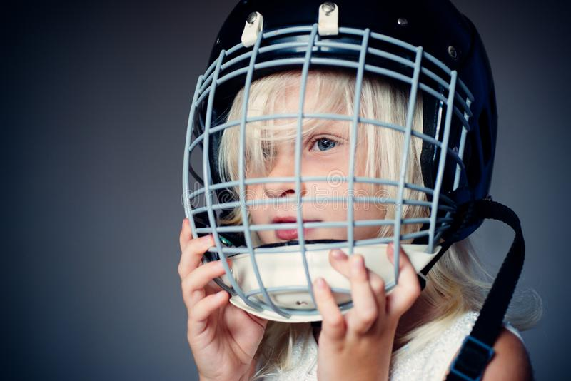 Girl cute child wear hockey helmet close up. Safety and protection. Protective grid on face. Sport equipment. Hockey or. Rugby helmet. Sport childhood. Future stock images