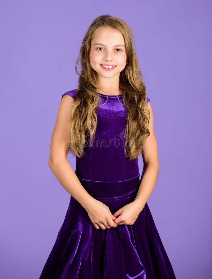 Girl cute child wear velvet violet dress. Clothes for ballroom dance. Kids fashion. Kid fashionable dress looks adorable. Ballroom dancewear fashion concept stock photography