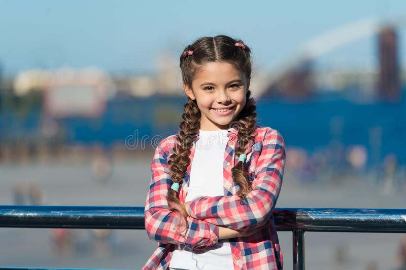Girl cute kid with braids relaxing urban background defocused. Organize activities for teenagers. Vacation and leisure royalty free stock images
