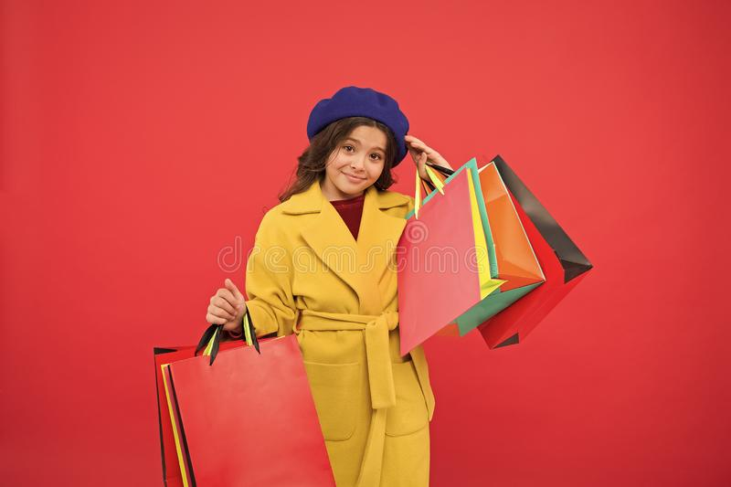 Girl cute kid hold shopping bags red background. Get discount shopping on birthday holiday. Fashionista adore shopping royalty free stock photography
