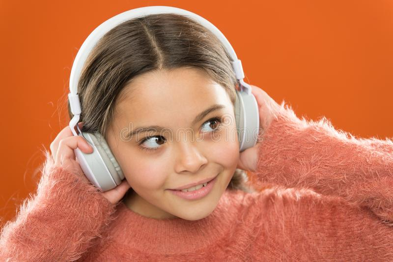 Girl cute little child wear headphones listen music. Kid listen music orange background. Recommended music based on. Initial interest. Easiest way to find new stock photos