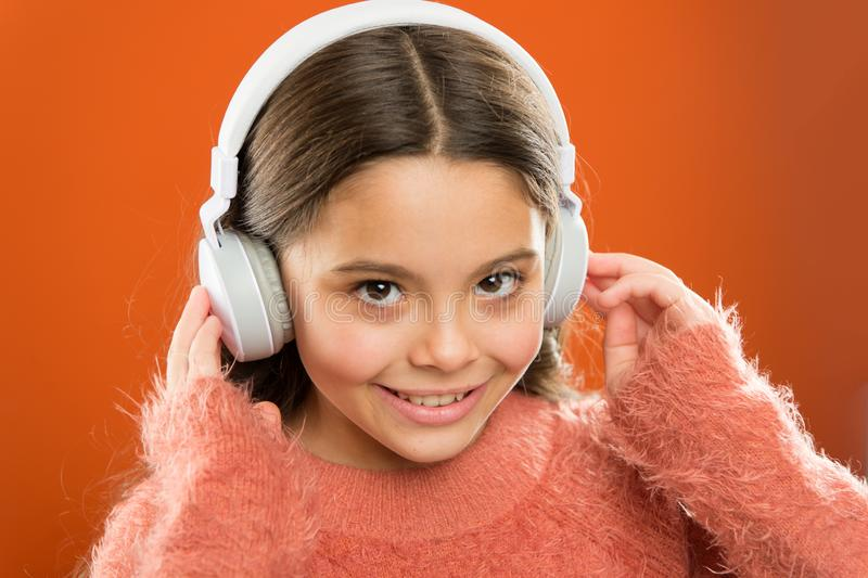 Girl cute little child wear headphones listen music. Kid listen music orange background. Recommended music based on. Initial interest. Tell me what you listen stock photo