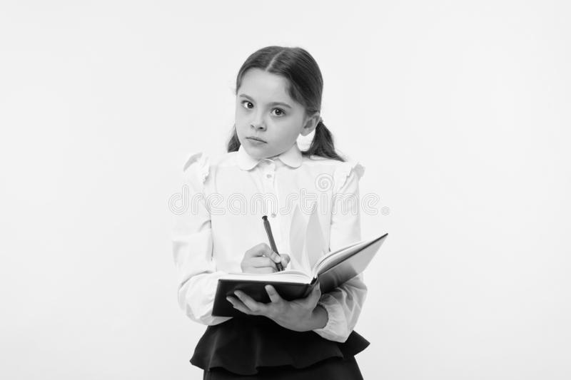 Girl cute schoolgirl in uniform hold book with information yellow background. Pupil get information from book. Child. Wear school uniform prepare for lesson stock image