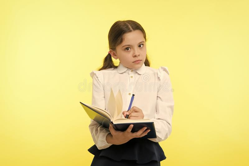 Girl cute schoolgirl in uniform hold book with information yellow background. Pupil get information from book. Child. Wear school uniform prepare for lesson stock images