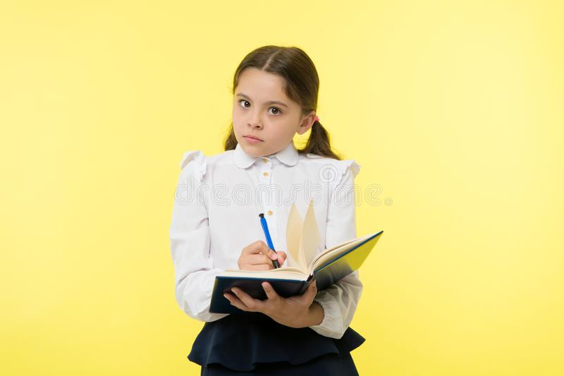 Girl cute schoolgirl in uniform hold book with information yellow background. Pupil get information from book. Child. Wear school uniform prepare for lesson royalty free stock images