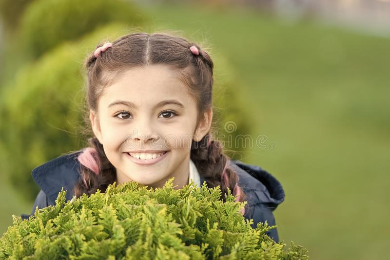 Girl cute smiling kid green grass background. Healthy emotional happy kid relaxing outdoors. What makes child happy royalty free stock image