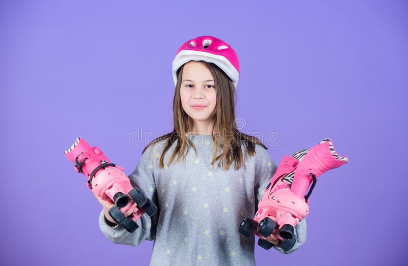 Girl cute teen wear helmet and roller skates on violet background. Active leisure and lifestyle. Roller skating teen stock photos