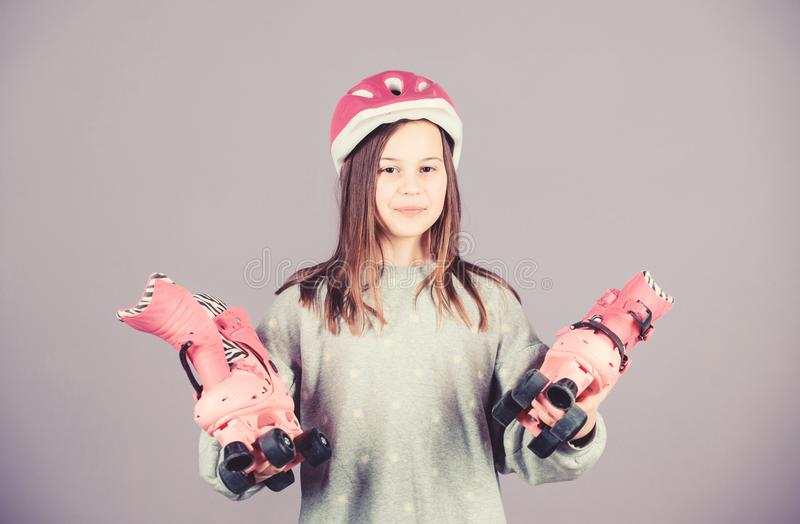 Girl cute teen wear helmet and roller skates on violet background. Active leisure and lifestyle. Roller skating teen. Hobby. Joyful teen going to ride. Sporty stock image